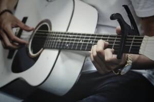 En man spelar akustisk gitarr